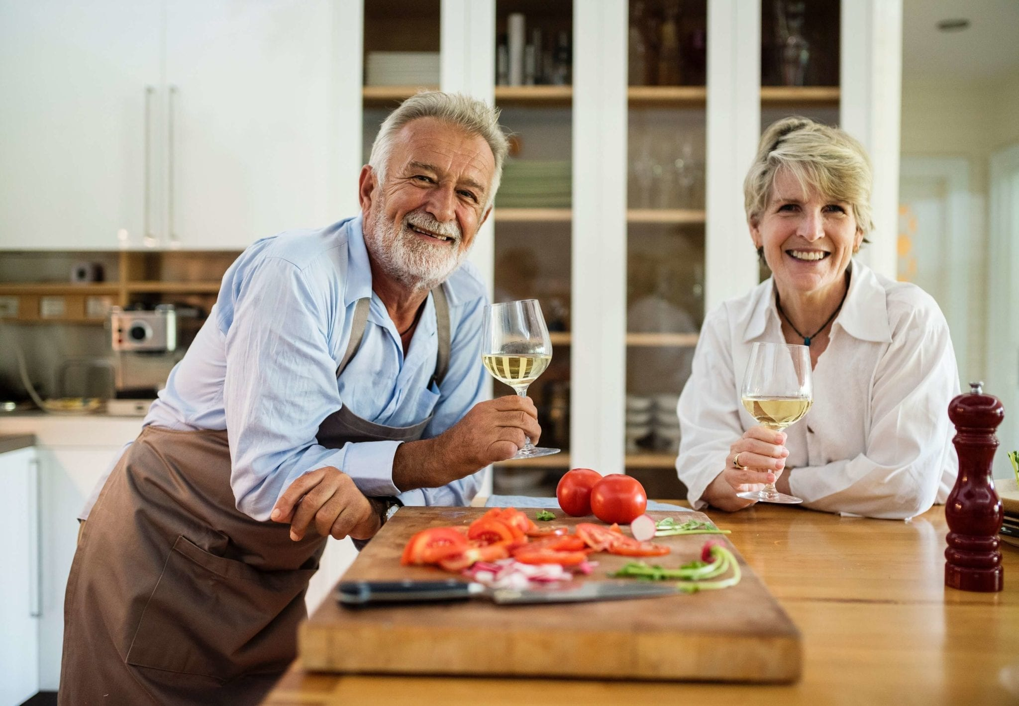 Two older adults enjoy wine and vegetables in their kitchen
