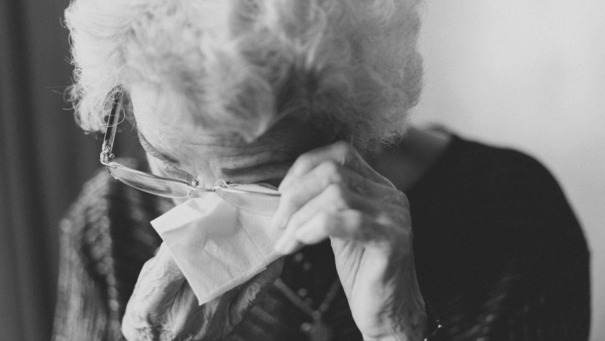 black and white photo of elderly woman crying